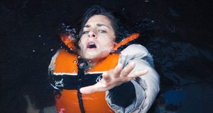 woman in flotation vest falling under water