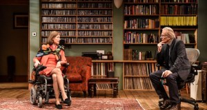 A lady in a wheelchair and a man face each other in a book-filled office