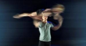 Male dancer holding female dancer horizontally above his head