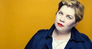Portrait of Comedian Katy Brand in front of a vibrant yellow backdrop
