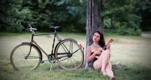 woman leaning on tree with bicycle beside her