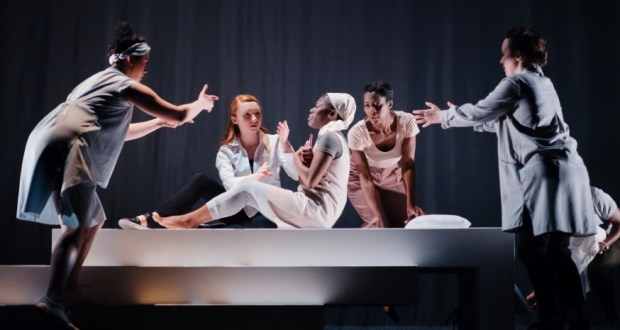 Four woman reaching towards a fifth at their centre