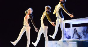 Three dancers dressed as penguins step out