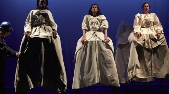 Three women in white dresses and on stilts. One soldier