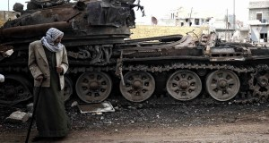 Arabic man next to wreckage of tank