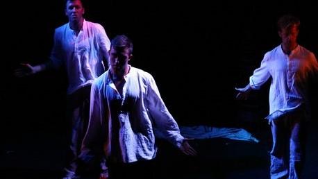 Three men in white shirts dark background