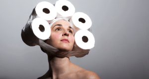 woman with five toilet rolls stuck to her head