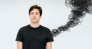 man in balck t shirt in front of white wall with black scribbles