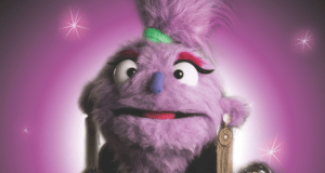 purple furry puppet woman with gold earrings