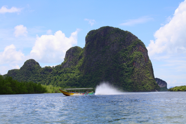 a long tail boat in front of a limestone mountain in Phang Nga Bay, Thailand