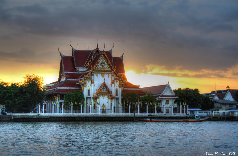 Wat Rakhang at sunset on the Chao Phraya River in Bangkok, Thailand