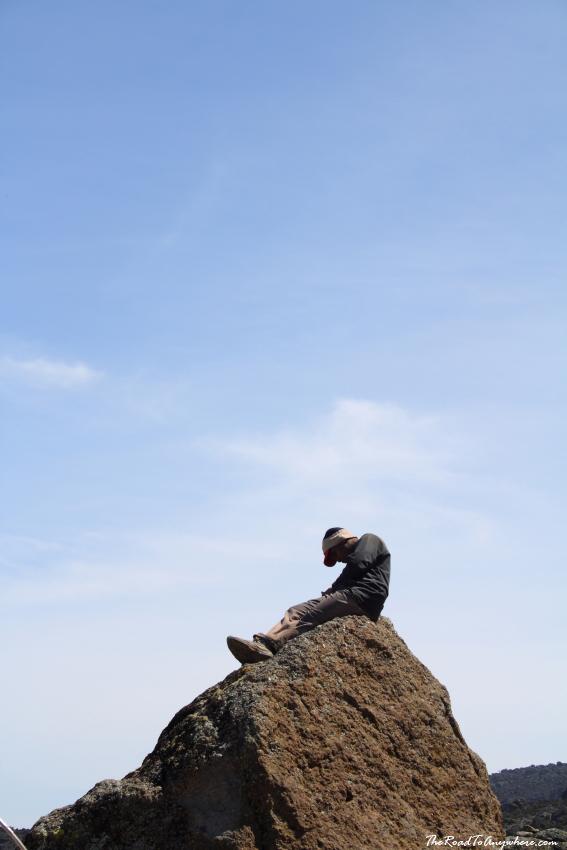 A porter resting on a rock at Karanga Camp on Mount Kilimanjaro, Tanzania