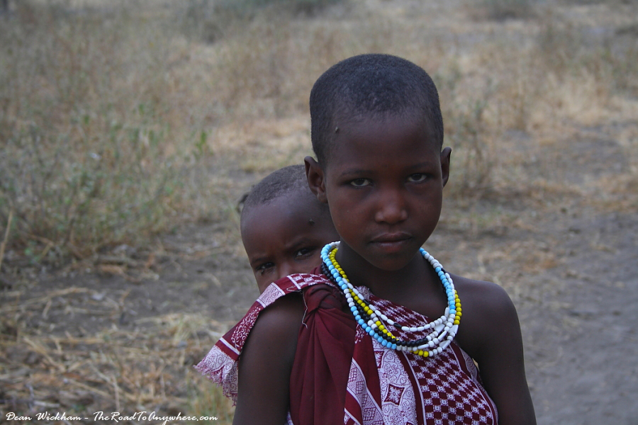 A Masai girl with her baby brother on her back in a Masai Village in Tanzania