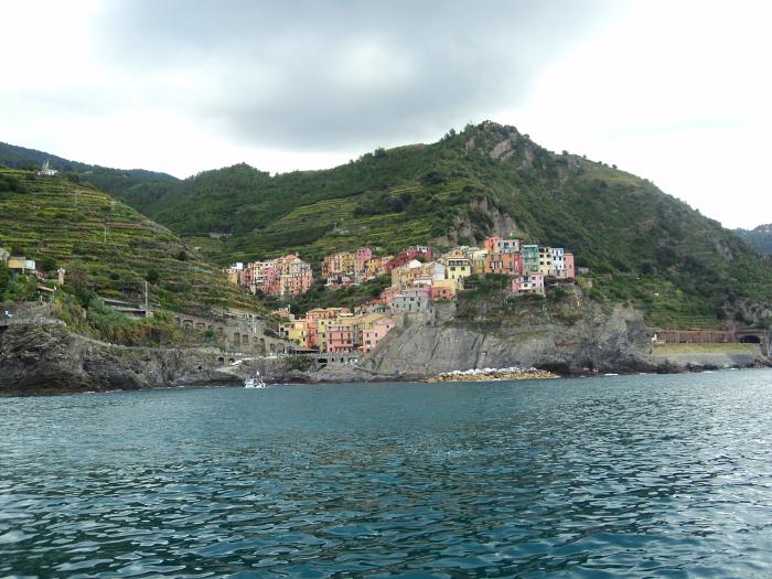 View of Manarola from the sea on the way to Riomaggiore Riomaggiore in Cinque Terre, Italy