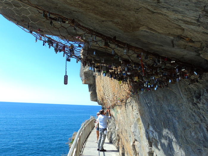 People placing a love lock on Via Dell'Amore in Cinque Terre, Italy
