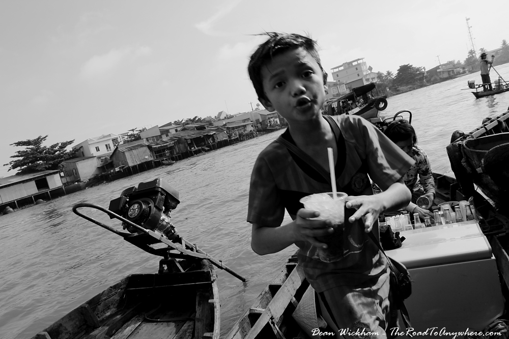 A kid selling coffee at Cai Rang Floating Market in the Mekong Delta, Vietnam