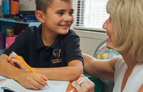boy student learning from teacher smiling and writing