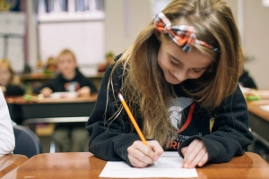 girl sitting at desk writing and smiling at school