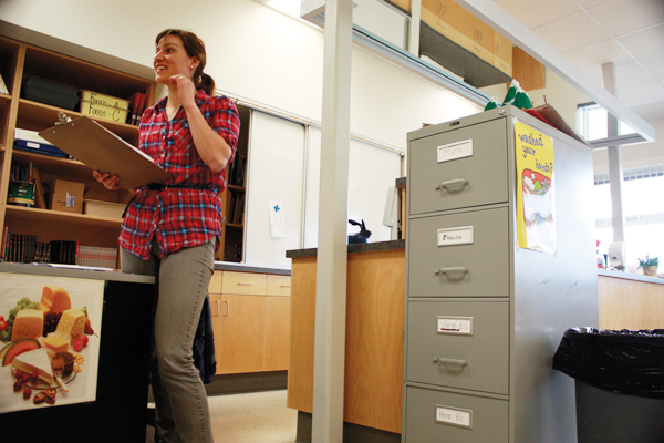 Valemount Secondary teacher Jean Ann Berkenpas with her file cabinet arranged by the subjects she teaches: math, outdoor education, home economics, and English.