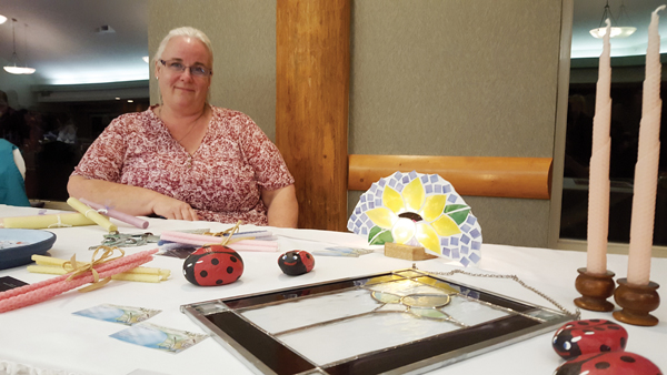 Photo by Laura Keil Hollie Blanchette had a table at the  home-based business mini trade show at the Chamer of Commerce meeting last week. She showcased her stained glass and her daughter's beeswax candles.