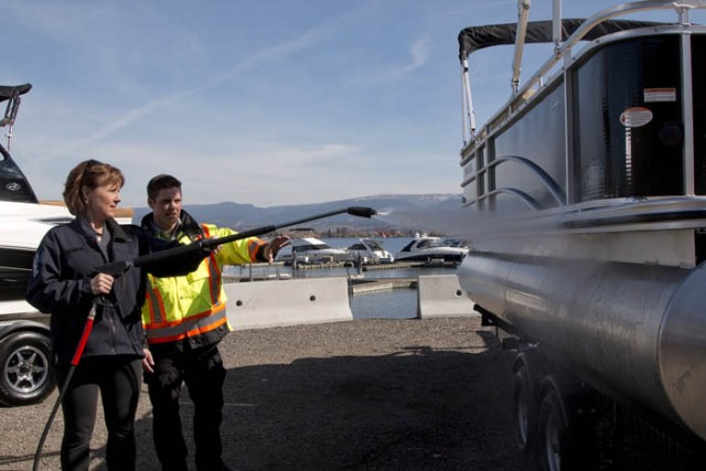 BC Premier Christy Clark pitches in, pressure-washing watercraft to dislodge any mollusc hitchhikers.