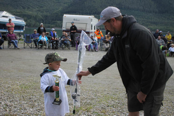 Mason Lewis is presented his trophy by Marina Association president, Owen Torgerson. Lewis won the 6 and under category.