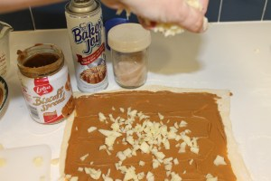 Sprinkling diced apples over the Biscoff covered pastry.