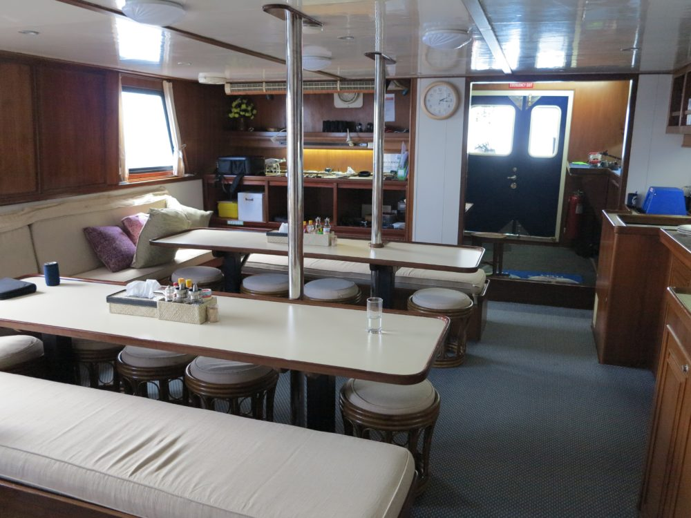 Raja Ampat Aggressor Dining room with two large tables and room for 16 people.