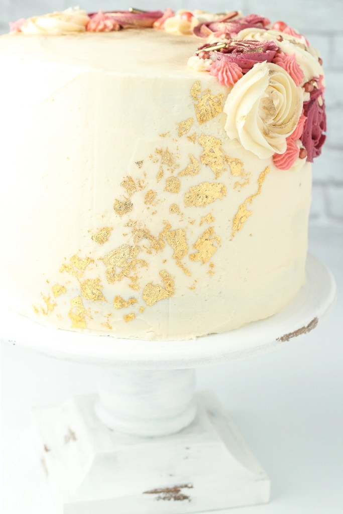 A vegan german chocolate cake decorated with edible gold leafing down the side.