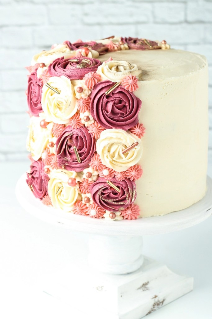 A vegan german chocolate cake decorated with pink rosettes and gold sprinkles.