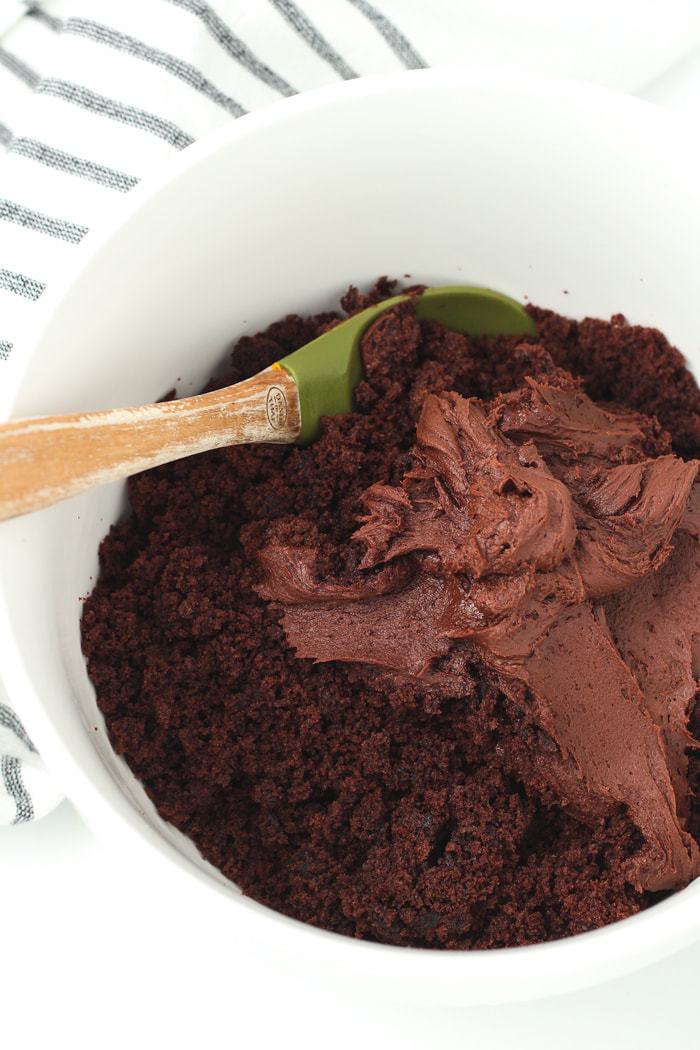 Crumbled chocolate cake in a bowl with chocolate frosting and a spoon mixing them together.