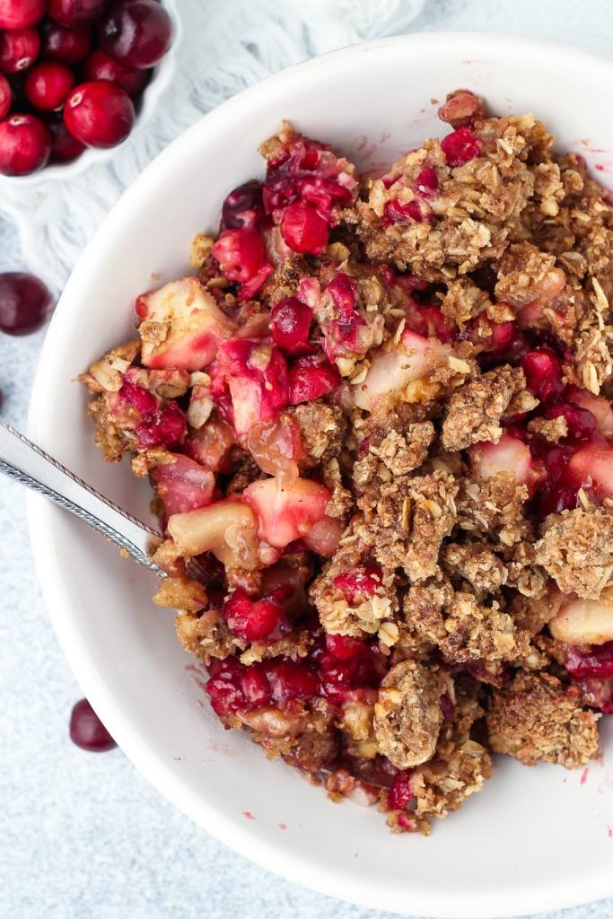 Cranberry Apple Pear Crisp in a bowl with a spoon.