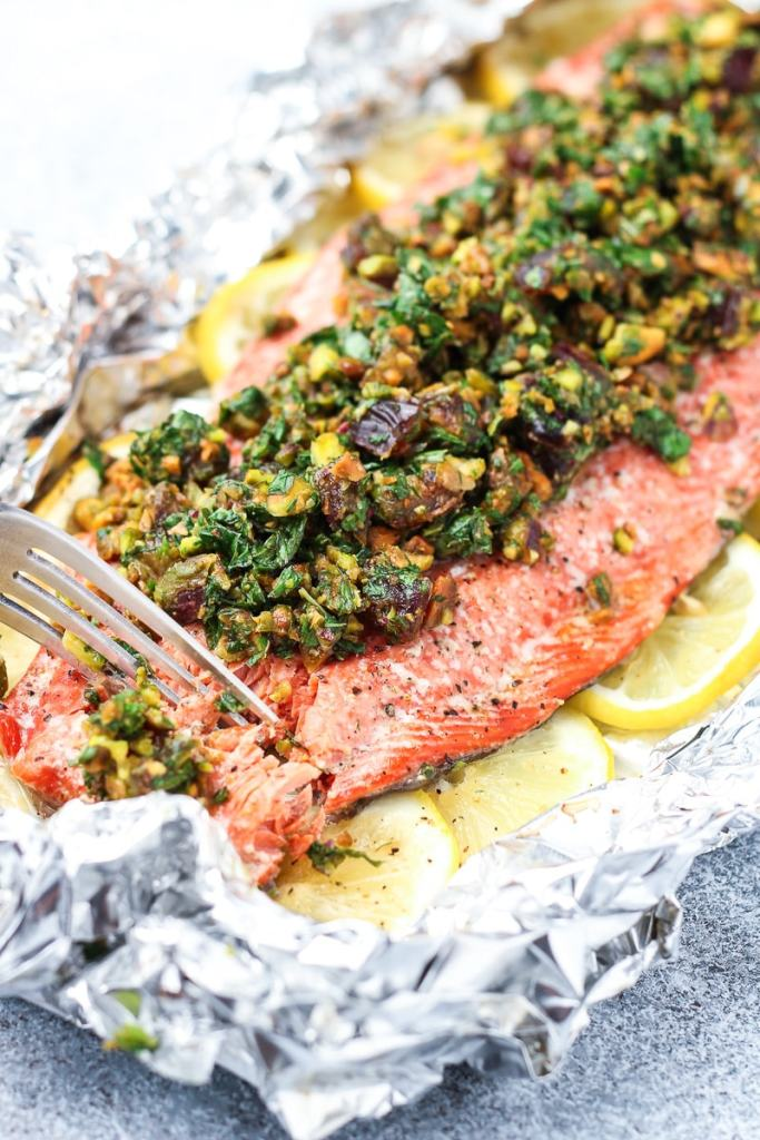 A fork cutting into the oven baked salmon topped with a pistachio and herb gremolata.