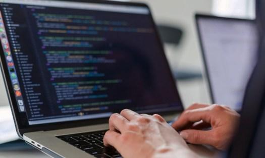 Drupal website developer coding on laptop