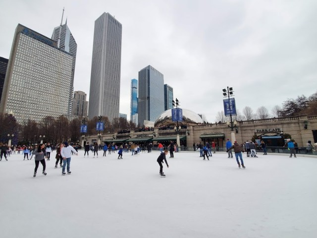 people outdoor skating at McCormick Tribune Ice Rink in Chicago with The Bean in the background