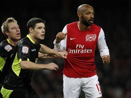 Arsenal's Thierry Henry is marked by Leeds United's Luciano Becchio and Darren O'Dea during their FA Cup soccer match at the Emirates Stadium in London