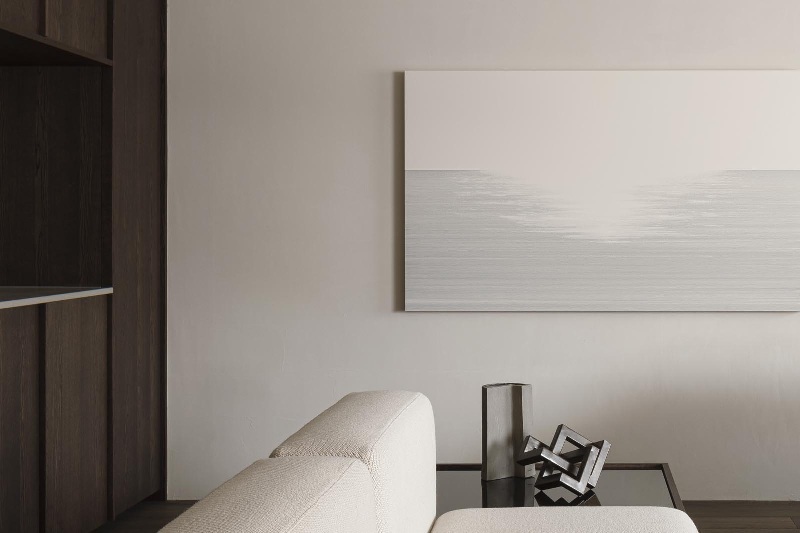 Minimalist Japandi living room with dark wooden panelling, beige sofa and neutral earthy tones | These Four Walls blog