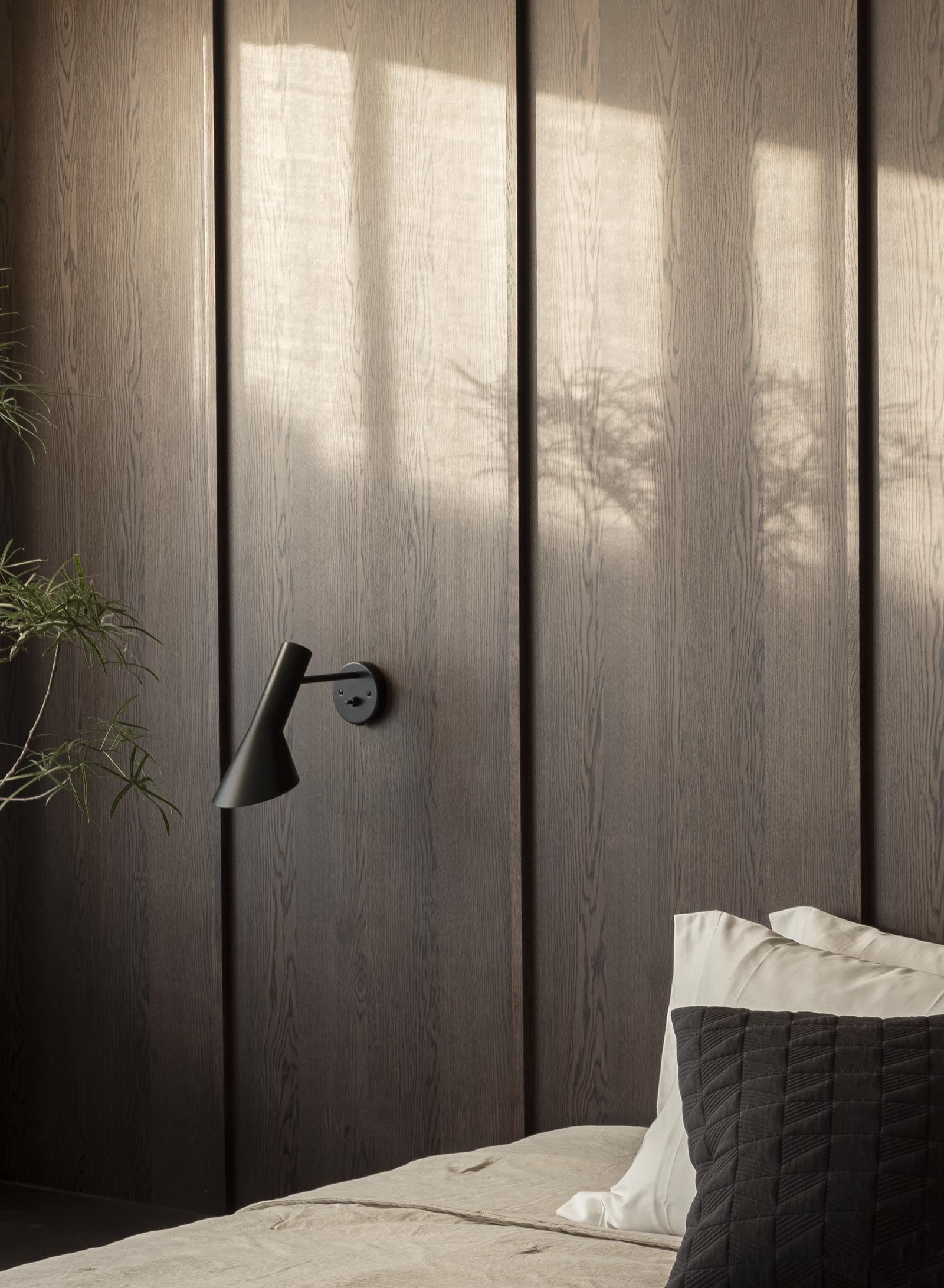Minimalist Japandi bedroom with dark wooden wall panelling and neutral earthy tones | These Four Walls blog