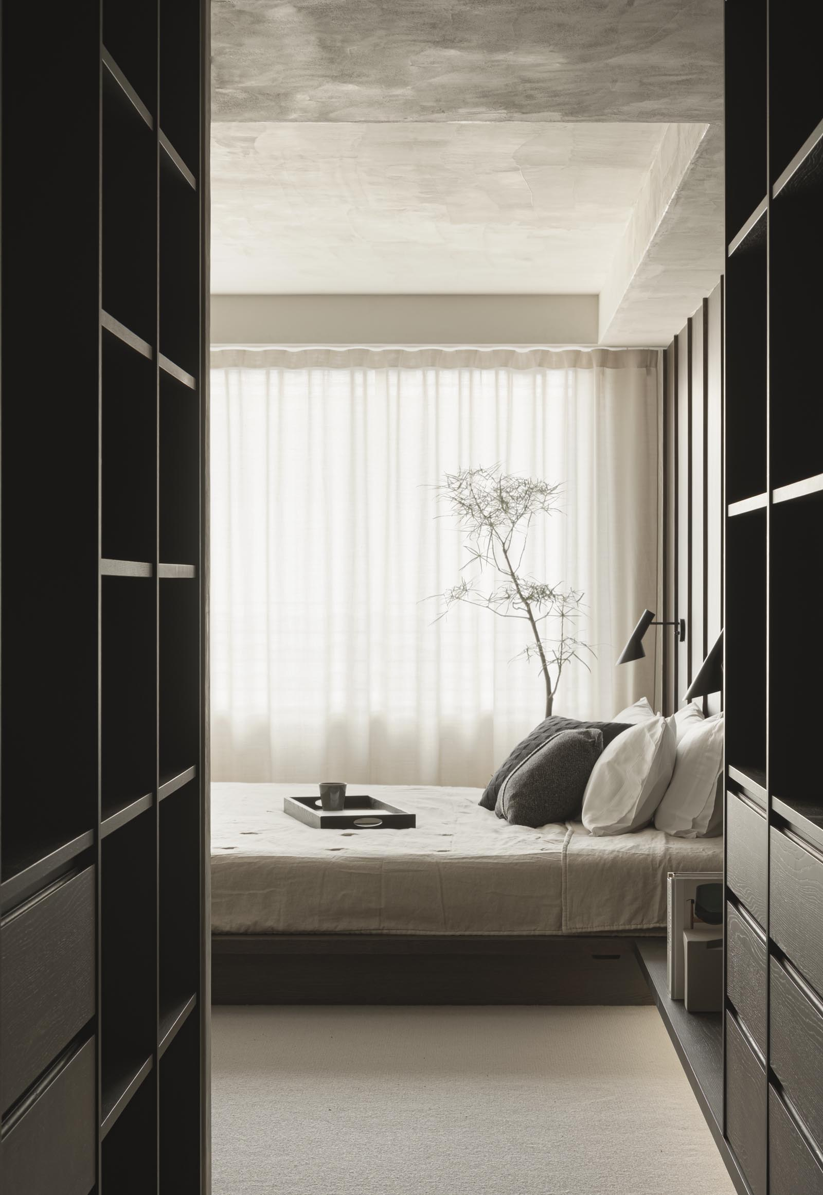 Minimalist Japandi bedroom with dark wooden panelling, bespoke cabinetry and neutral earthy tones | These Four Walls blog