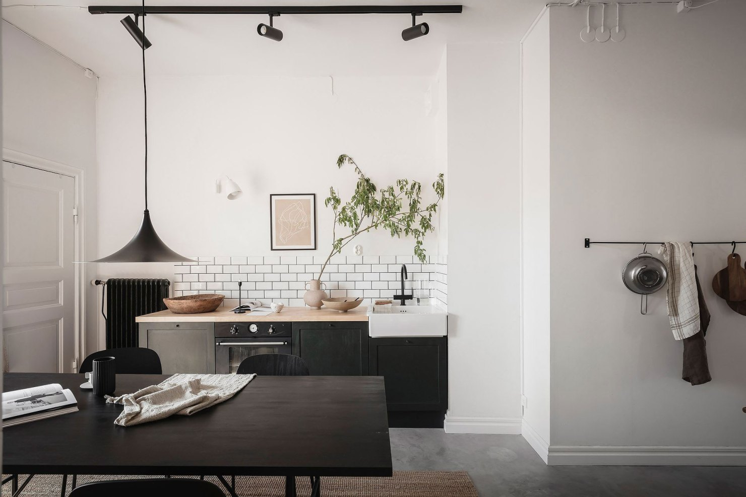 Minimalist monochrome kitchen with open-plan dining area, black units, wooden worktops and white metro tiles   How to design a lighting scheme that works for you   These Four Walls blog
