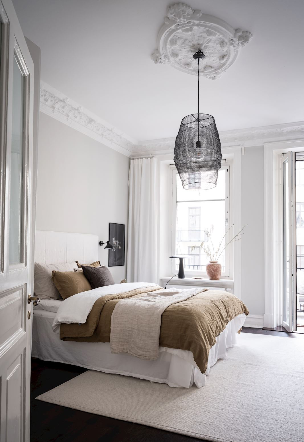 Minimalist white bedroom in a period apartment, with black pendant light and accessories in earthy neutrals   How to design a lighting scheme that works for you   These Four Walls blog