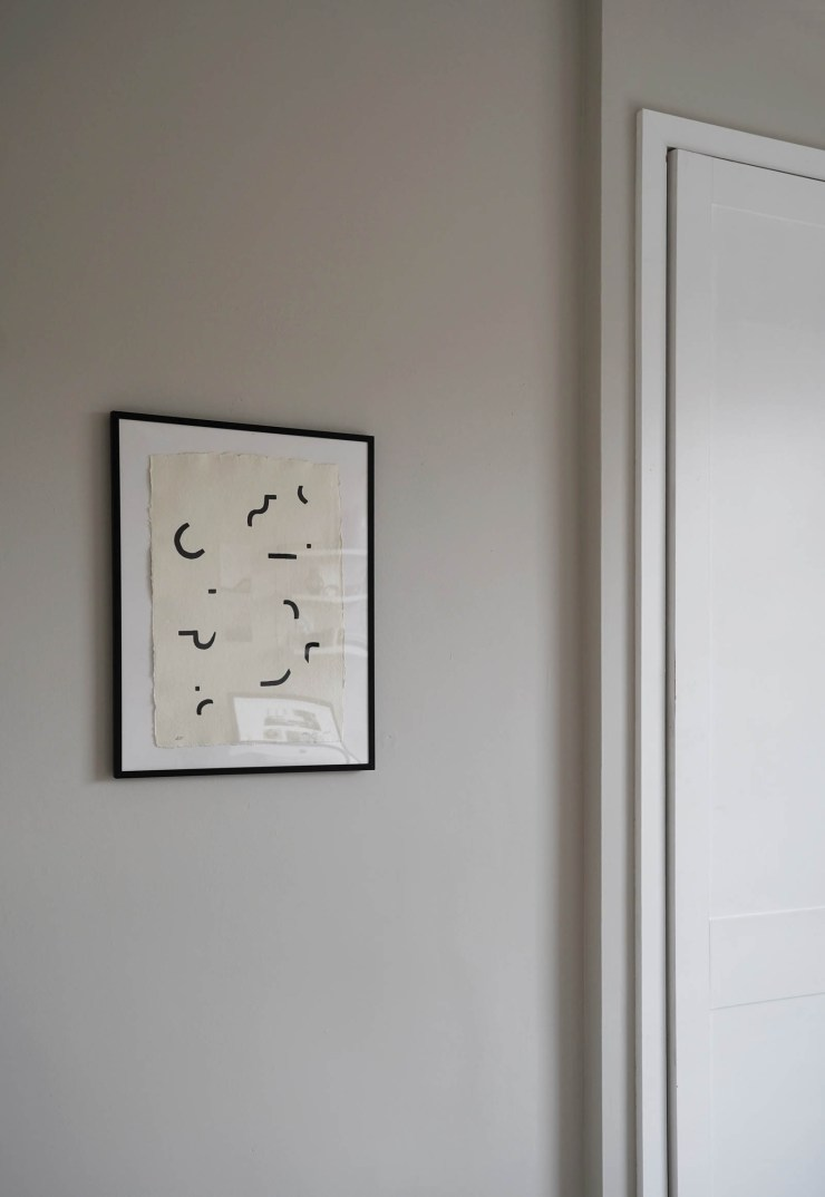 Soft grey walls and beige and black abstract artwork in a minimalist home office   These Four Walls blog