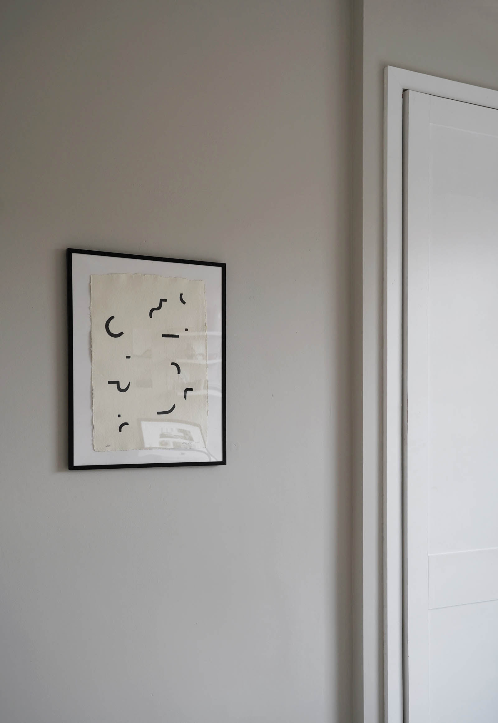 Soft grey walls and beige and black abstract artwork in a minimalist home office | These Four Walls blog
