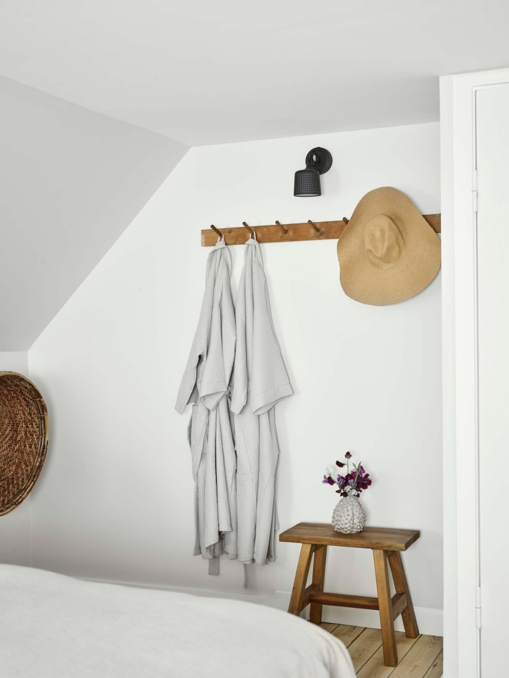 Minimalist white bedroom with peg rail and vintage stool at the Vipp Farmhouse - a designer holiday cottage in the Danish countryside   These Four Walls blog