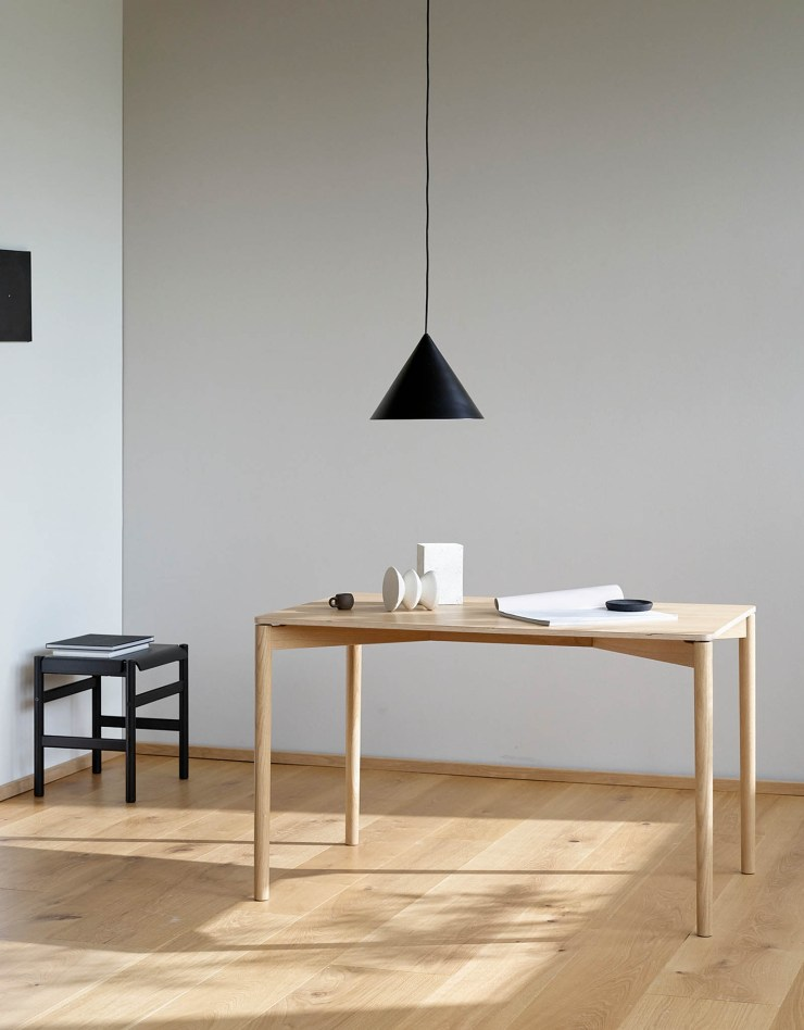 Minimalist dining room featuring TAKT's 'Cross 120' oak table, shown here with a contemporary black pendant light and stool | These Four Walls blog