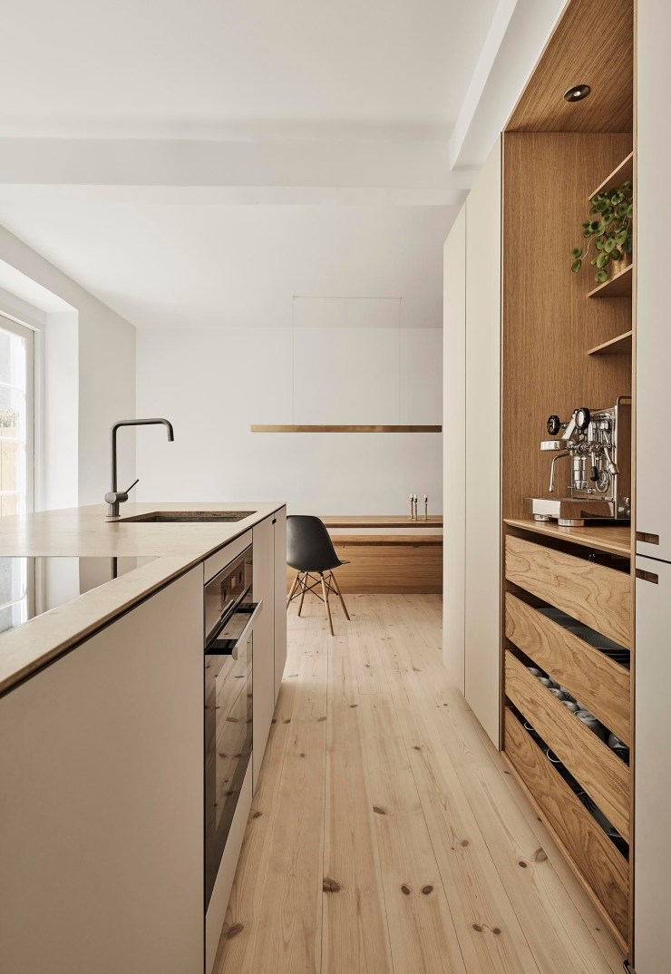 A warm, minimalist kitchen in beige and oak, with open niche, display shelves and built-in dining area   These Four Walls blog