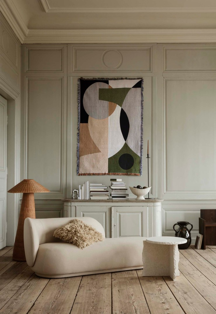 Soft green and beige living room with panelled walls, curved sofa, abstract tapestry wall hanging, marble side table and earthy neutral tones | The autumn-winter 2021 collection from Ferm Living | These Four Walls blog