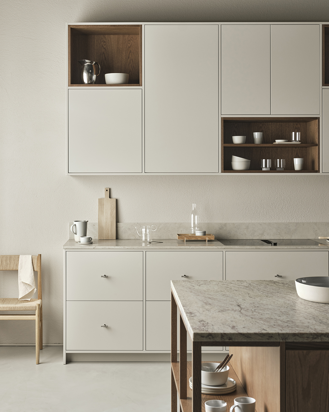 Minimalist grey kitchen with stone worktops, sections of open shelving, oak accents and beige walls | Eight inspiring kitchen ideas from Nordiska Kök's new showroom | These Four Walls blog