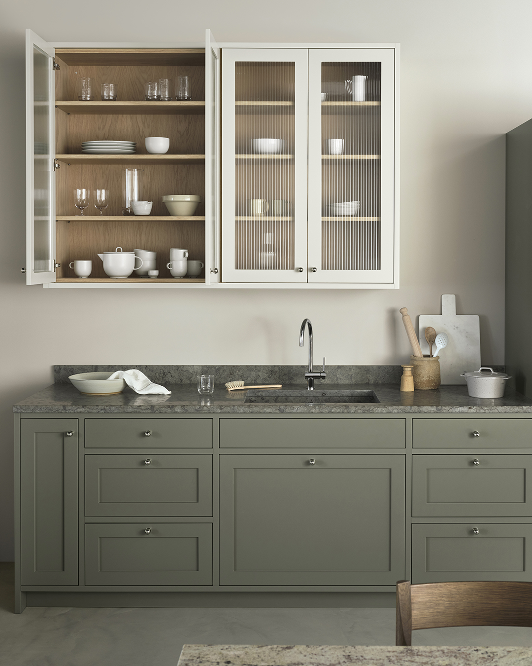 Elegant two-colour kitchen with fluted glass doors, marble worktops and classic Shaker-style units in stone grey and olive green | Eight inspiring kitchen ideas from Nordiska Kök's new showroom | These Four Walls blog