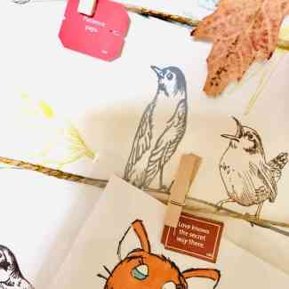 section of a noticeboard with printed images of birds, an autumnal leaf and two yogi tea tags one reads: patience pays, the other: love knows the secret way there